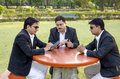 Three businessmen discussing business plan in park sitting on a bench and Stock Photos