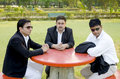 Three businessmen discussing plan in park sitting on a bench and business Royalty Free Stock Images