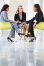 Three Businesswomen Meeting Around Table In Modern Office Royalty Free Stock Photos