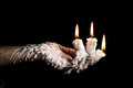 Three candle sticks on fingers buring artistic conversion with wax flow Royalty Free Stock Photos