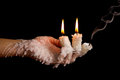 Three candle sticks on fingers buring smoulder with wax flow dead Stock Photo