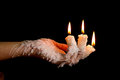 Three candle sticks on fingers buring with wax flow Royalty Free Stock Photo