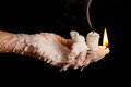 Three candle sticks on fingers buring with wax flow Royalty Free Stock Photography