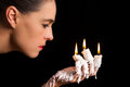 Three candle sticks on fingers buring with wax flow face blow blowing Royalty Free Stock Photos
