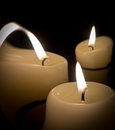 Three candles on a glass surface with some abstract flame on one of them Stock Photography