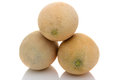 Three cantaloupes stacked over a white background with reflection Stock Images