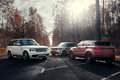 Three cars Land Rover Range Rover parked at autumn forest asphalt road at sunny daytime Royalty Free Stock Photo