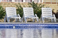 Three chaise longues recreation background near the pool Royalty Free Stock Image