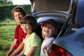 Three cheerful child sitting in the trunk of a car on nature Royalty Free Stock Images