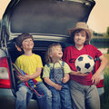 Three cheerful child sitting in the trunk a car on of nature Stock Image