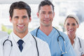Three cheerful doctors standing in a bright hospital Stock Images