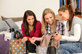 Three cheerful girls with clothes from sale shopping bags Royalty Free Stock Photo