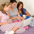 Three cheerful girls surfing on the net Royalty Free Stock Photo