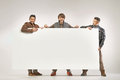 Three cheerful guys holding the board Royalty Free Stock Photo