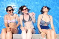 Three cheerful young women simulate that they sit over a pools edge with a water wall backwards Royalty Free Stock Photo