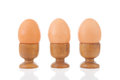 Three chicken eggs in a row in wooden holders Royalty Free Stock Images