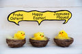 Three chicks with comic speech balloon with german french and english happy easter sitting in baskets or nest yellow feathers on Royalty Free Stock Photography