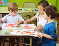 Three children painting with watercolor on paper in a kindergarten Stock Photo