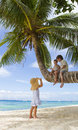 Three children on palm tree Stock Images
