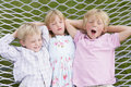 Three children relaxing and sleeping in hammock Royalty Free Stock Image