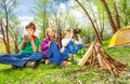 Three children resting near the wooden bonfire Royalty Free Stock Photo