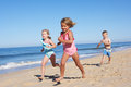 Three Children Running Along Beach Stock Images