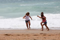 Three children running at the beach having an awesome time along Royalty Free Stock Photography