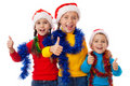 Three children in Santa hats with thumb up sign Stock Image