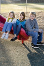 Three children sitting on slide Royalty Free Stock Images