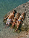 Three children sunbathing on rock at sea Stock Photo
