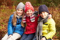 Three children on walk through winter woodland with arms around each other smiling Stock Images