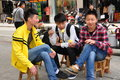 Three chinese teenagers seated on tiny wooden benches eating fresh pineapple slices in pengzhou china Royalty Free Stock Photos