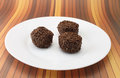 Three chocolate truffles on a white plate with tasty ready to enjoy dessert Royalty Free Stock Image