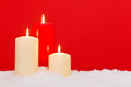 Three christmas candles red background sitting on snow against a Royalty Free Stock Photos