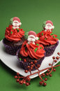 Three christmas cupcakes against a green background vertical in purple polka dot wrapper with red frosting and santa decoration Stock Images