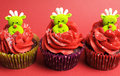 Three christmas cupcakes with fun and quirky reindeer faces face toppings in modern festive red lime green colors for Royalty Free Stock Photos