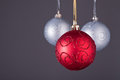 Three christmas decorations red decoration balls on grey background Stock Photo