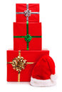 Three Christmas presents and Santa Claus hat. Royalty Free Stock Photo