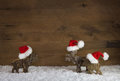 Three christmas reindeer of handmade wood with red white santa h Royalty Free Stock Photo