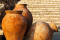 Three clay ancient amphora terracotta a standing in the garden stone wall in the background Royalty Free Stock Image