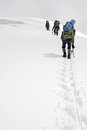 Three climbers ascend the glacier to top of mountain titnuld Stock Image
