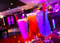 Three cocktails in a bar on wooden table with background Royalty Free Stock Images