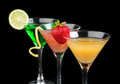 Three cocktails cosmopolitan cocktails decorated with citrus lem lemon twist yellow martini drink strawberry isolated on a black Stock Images