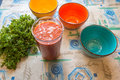 Three colored bowls next to greenery and jug of tomato juice Royalty Free Stock Photo