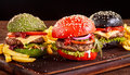 Three colorful Asian burgers with French Fries Royalty Free Stock Photo