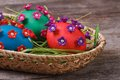 Three colorful Easter eggs with beautiful flowers in a basket