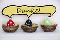 Three colorful easter eggs with comic speech balloon with danke means thank you red black and green dotted in baskets or nest on Stock Photography