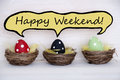 Three colorful easter eggs with comic speech balloon with happy weekend red black and green dotted in baskets or nest on white Stock Images