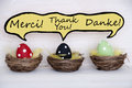 Three colorful easter eggs with comic speech balloon with thank you in french english and german red black green dotted baskets or Stock Photo