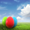 Three colorful eggs on a green field Stock Photos